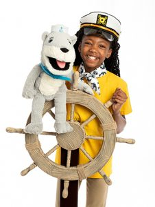 Black preteen girl in captain's hat, holding Oliver T. Otter puppet and one hand on a ship's wheel