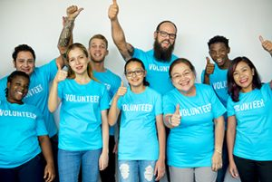 One adult male and several upbeat teen guys and teen girls are wear blue shirts with VOLUNTEER written on them