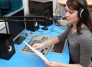 woman wearing headphones and reading into a microphone
