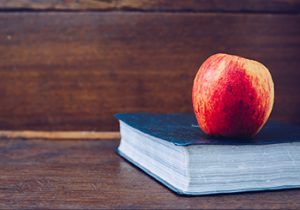 Red apple resting on Bible sitting on a table