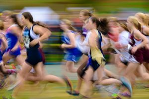 blur of girl runners competing in track