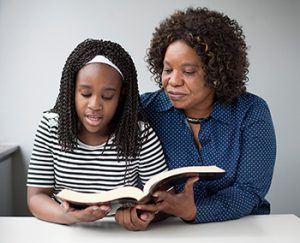 Balck woman looking on as black girl reads from Bible