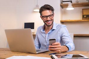 Man wearing glasses smiles at something on phone, perhaps a one-liner