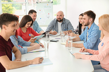 men and women around a business table