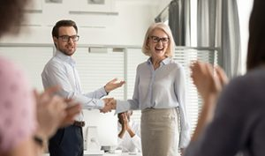 Man points to woman (in a presentation style) while he shakes her hand