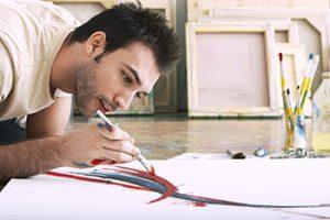 Man bent over paper he is painting