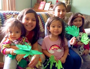 2 preschoolers, 2 older students holding paper palm branches for Palm Sunday