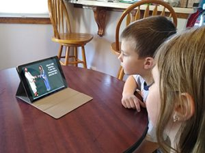 Middler brother and sister watch PowerPoint SS slideshow on laptop