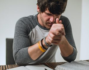 Man praying over Bible and lesson manual