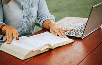 Open Bible next to laptop with woman's hands on each side of the Bible