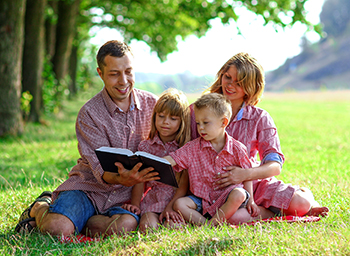 Family of four (dad, mom, boy, girl) sit on grass with open Bible in hand