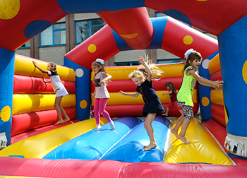 Colorful bouncy house with four kids in it