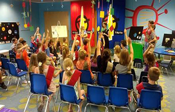 Kids with raised hands during a K4T meeting.